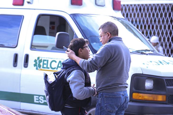 Édesapa gyerekével az iskola előtt, ahol egy 11 éves fiú megsebesítette hat társát, lelőtte tanárát, majd öngyilkos lett.