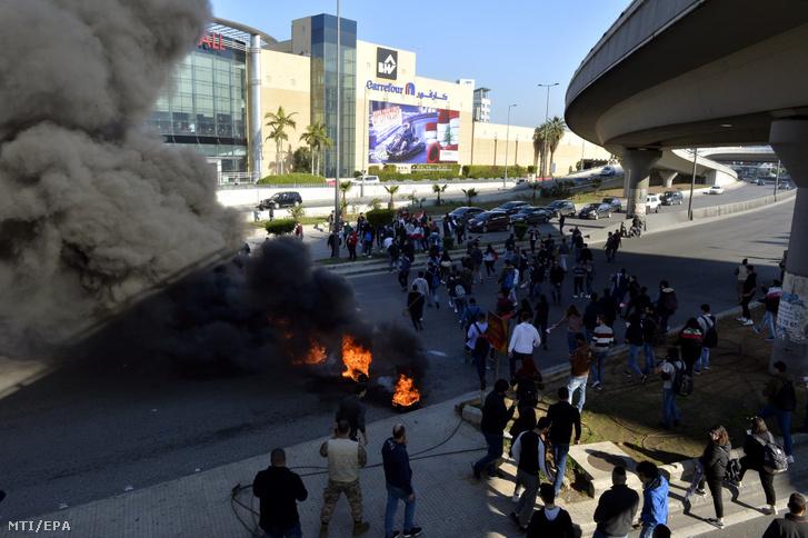 Kormányellenes tüntetők által felgyújtott útakadály ég Bejrútban