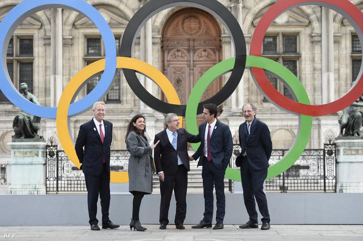 Guy Drut, a Nemzetközi Olimpiai Bizottság tagja, Anne Hidalgo Párizs polgármestere, Thomas Bach NOB-elnök, Denis Masseglia és Tony Estanguet a párizsi városháza előtt felállított olimpia gyűrűknél 2017. október 22-én