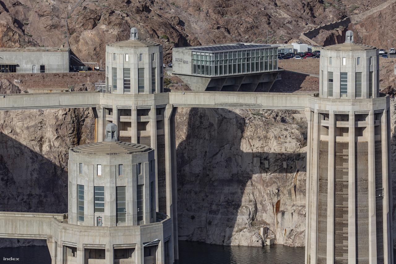 """Az erőmű turbináira négy torony vezeti a Colorado-folyó felduzzasztott vizét (a képen közülük három látható). A nevadai oldal két tornya közt a gát régebbi ajándékboltja és étterme, a nyolcvanas évek második felében épült Spillway House látható. A megnövekedett látogatószám miatt bezárták, kicsit arrébb új, nagyobb """"büfét"""" építettek helyette, 2017-ben pedig felújítva, már mint exkluzív rendezvényközpontot nyitották meg újra."""