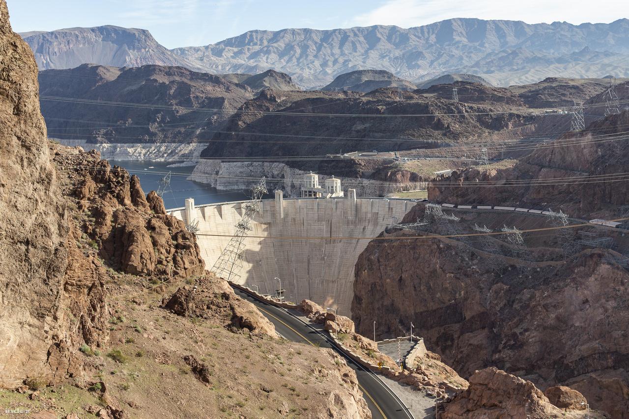 A vízerőmű fő elemét, a 221,3 méter magas gátat kevesebb mint két év alatt építették meg: 1933. június 6-án kezdték építeni és 1935. május 29-én öntötték formába az utolsó adag betont. A fotón jól megfigyelhető a sziklafalak alján a világos színű mészkőkiválás, ami azt mutatja, hogy a 2010-es évek óta tartó aszályos időszaknak köszönhetően mekkorát csökkent a Mead-tó vízszintje.
