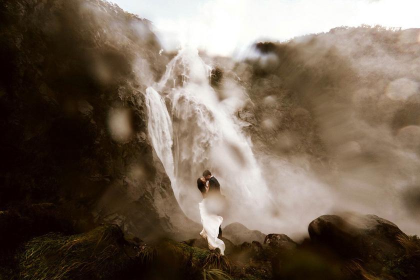 Egyszerűen lélegzetelállító hátteret nyújt a zubogó vízesés a szerelmes fotónak. A menyasszony ruhája szinte beleolvad a habokba.