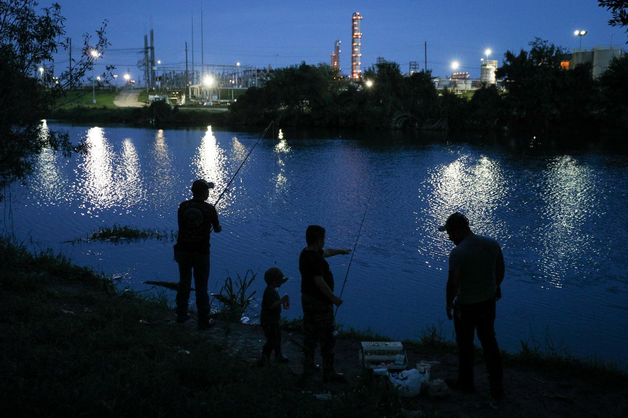 Horgászok a Houston-csatorna partján, szemben az olajfinomító fehér lángjai.