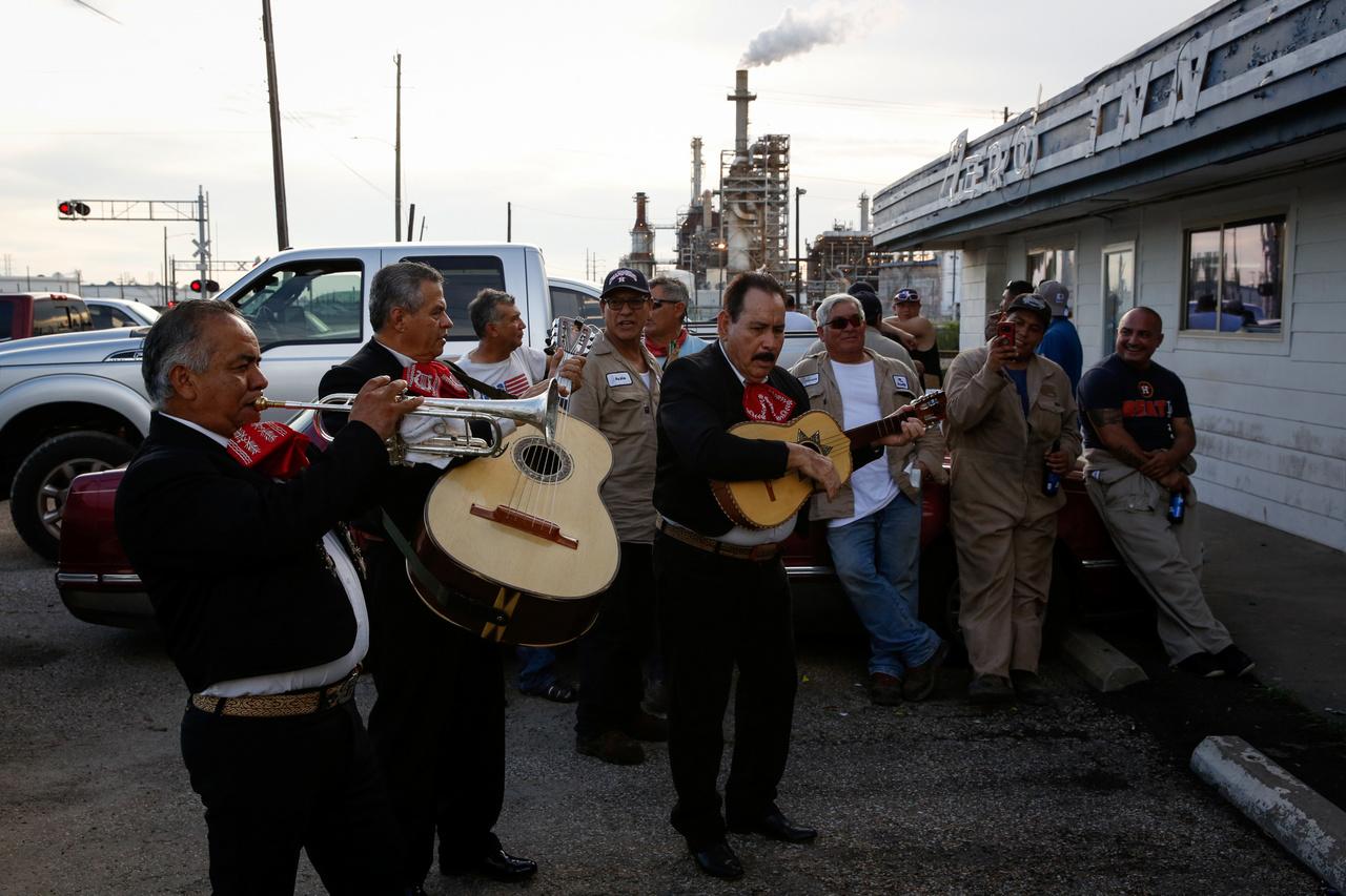 Mariachi zenekar várja az olajfinomítóból a műszak után kijövő dolgozókat. Manchester lakossága 97 százalékban latino származásúakból áll.