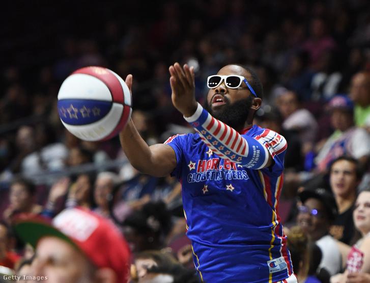 A Harlem Globetrotters játékosa indít egy dobást a nézőtérről alsó dobásos technikával bemelegítés közben