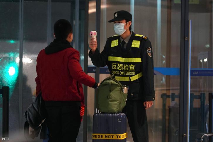 Infravörös hőmérővel méri egy távozó utas testhőmérsékletét egy dolgozó a vuhani nemzetközi repülőtéren 2020. január 21-én.