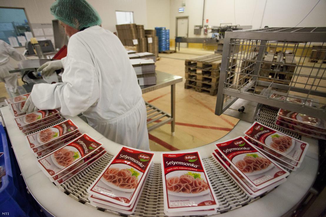 Selyemsonkát vesz le egy dolgozó a szállítószalagról a Sága Foods Zrt. sárvári gyárában