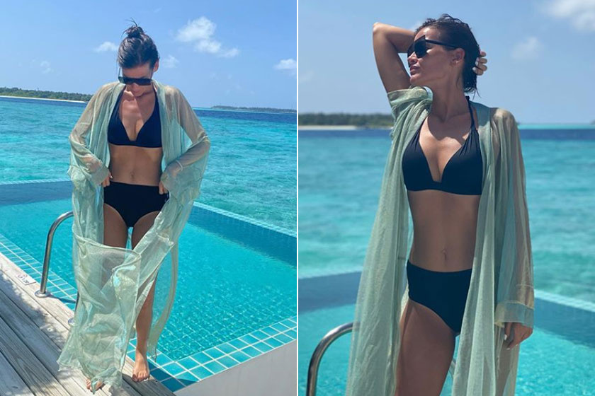 Andi úgy pózol a medencénél, mint egy modell. Büszke lehet alakjára.