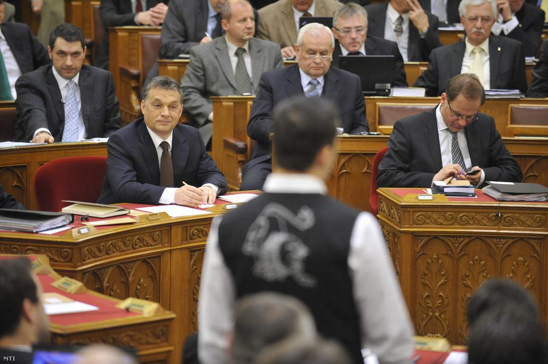 Vona Gábor, a Jobbik elnök-frakcióvezetője (háttal) gárdamellényben reagál Orbán Viktor beszédjére 2011. február 14-én