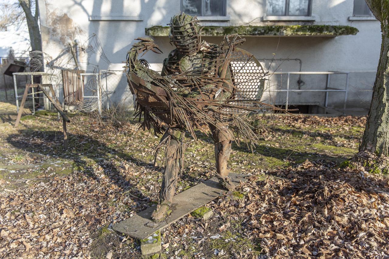 A főként hangszerszobrairól ismert Lois Viktor tatabányai szobrász alkotása (sokan ismerhetik Loist a Meteo című magyar kultfilmből is). A skanzenben 1997 óta rendezik meg nyaranta a KÉP-ZE-LET Nemzetközi Fémszobrász Szimpóziumot, az alkotásokból folyamatosan gyarapodó szoborkert jött létre, illetve Lois alkotásaiból megtekinthető egy szabadtéri, illetve az egykori fürdőépületben egy beltéri kiállítás is.