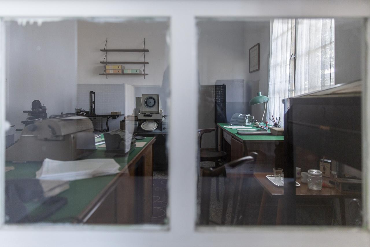 A bérszámfejtés irodája, fizetésnapon ennek ablakánál álttak sorba a vájárok, hogy felvegyék a munkájukért járó bért. Jobbra az asztalon, a klasszikus íróasztali lámpa alatt egy Triumphator mechanikus számológép, balra pedig egy névtáblanyomó gép látható. Ez utóbbival névjegykártya méretű fémtáblácskákat – úgynevezett címlemezeket – készítettek a bányászok nevével, személyi adataival, azonosító számával, ami aztán a nyilvántartás részeként bekerült a kartotékozóba, és például a névre szóló hivatalos borítékokra ezekkel nyomtatták a címzett dolgozó nevét.
