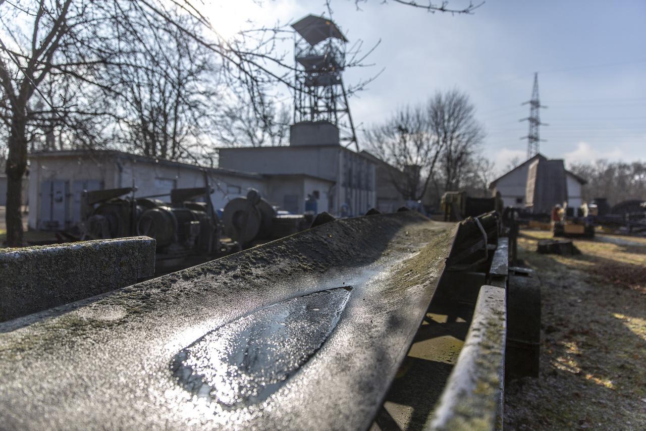 Apró tócsa olvadozó jéghártyával a skanzen szénszállító szalagján. A háttérben az egykori XV-ös akna acélszerkezetű tornya látható, ami a tatabányai szénmedence nyugati területén létesített első bányaüzem emlékét őrzi.