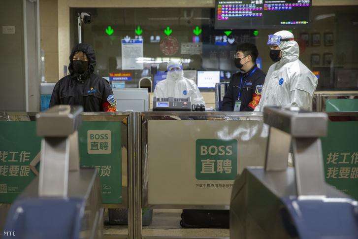 Védőruhát viselő munkások egy pekingi metróállomáson felállított ellenőrző pontnál 2020. január 24-én.