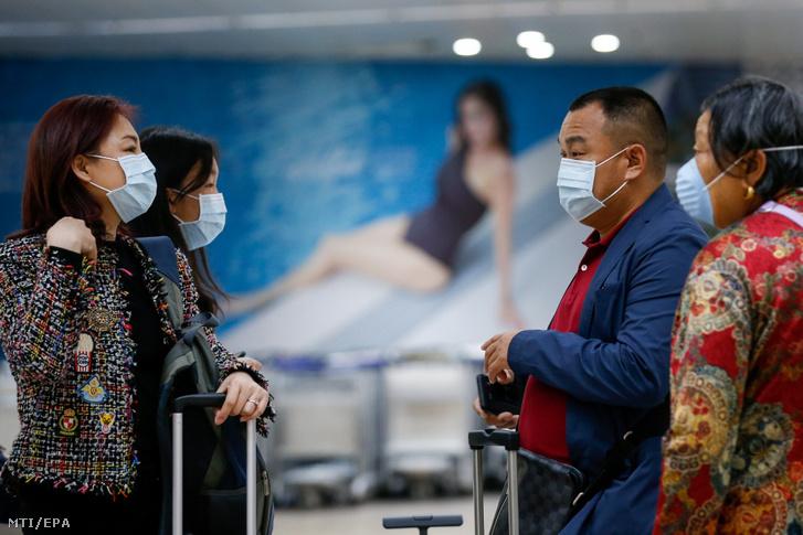 Védőmaszkot viselő kínai utasok várakoznak a belépésre a manilai Ninoy Aquino nemzetközi repülőtéren