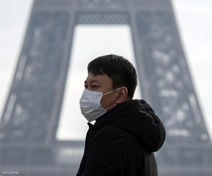 Az új tüdőgyulladást okozó koronavírus terjedése miatt szájmaszkot visel egy turista a párizsi Eiffel-toronynál 2020. január 25-én.