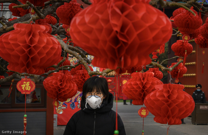 Egy kínai nő védőmaszkot visel egy holdújév alkalmából rendezett, de bezárt vásáron Pekingben 2020. január 26-án.