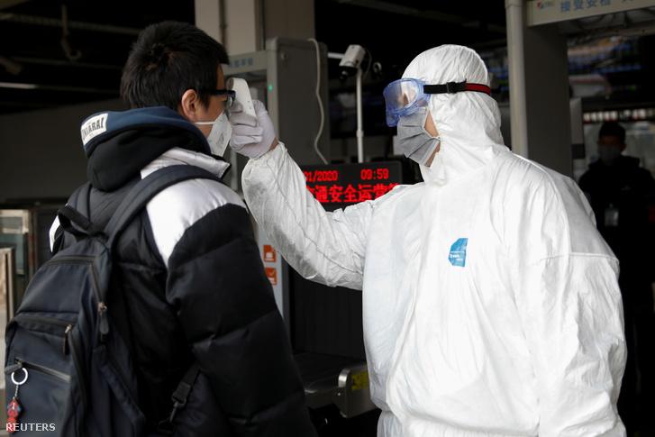 Thermométerrel ellenőrzik a testhőmérsékletet a Xizhimen mentróállomáson Pekingben 2020. január 27-én