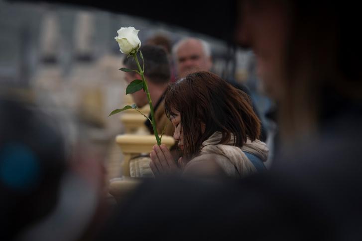 Hír, eseményfotó: 1.díj                         Dombóvári Tamás: RészvétEgy koreai nő egy szál feher rózsaval fejezi ki reszvétét a Hableány hajót ért baleset helyszínénél, Budapesten, a Margit hídon.
