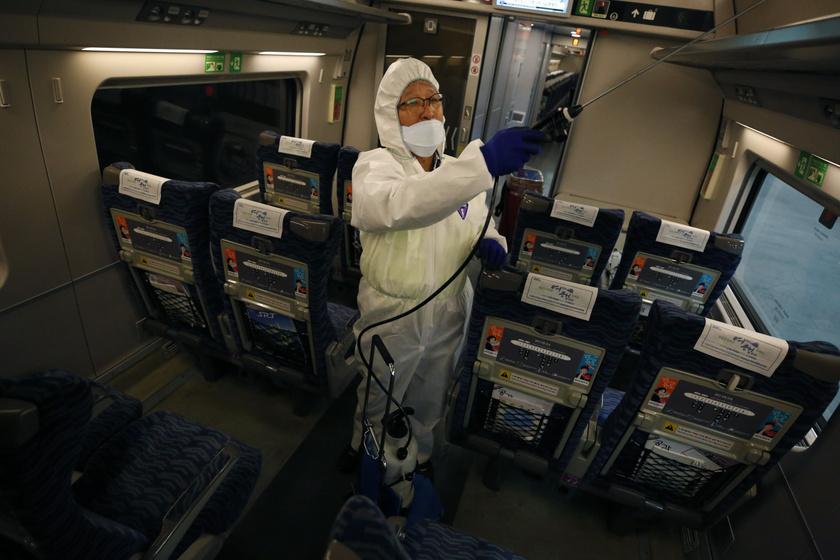 Egy szöuli pályaudvaron várakozó vonaton végez fertőtlenítést egy dolgozó.