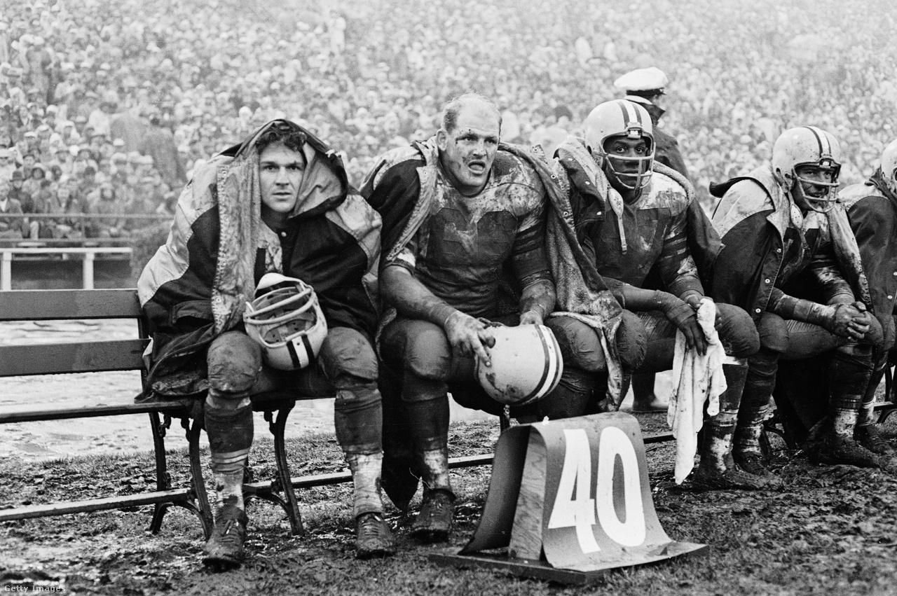 Pénz nem csak játékosokra, a pályákra sem nagyon volt az 1960-as években. A legutóbbi NFL-szezonban ugyan még mindig a rendes füves borítás volt fölényben a műfüves pályákkal szemben (19-13 arányban), bár ezek már szinte minden időjárási körülménnyel elbírnak. Ez persze nem volt mindig így, ezen az 1960-ban készült képen jól látszik, hogy tulajdonképpen bokáig érő sárban kellett dagonyázniuk a játékosoknak elég gyakran. A sisakját a kezében fogó, kopasz fejbúbjáról felismerhető Ray Nitschke mezén például alig olvasható a 66-os mezszám, amit később visszavonultatott a Green Bay Packers. Ray Nitschke ott volt a nagy NFL-történelem pillanatában, az első és a második Super Bowlban is nyert, és összesen ötszörös NFL-bajnok volt Vince Lombardi edző keze alatt. A legjobb NFL-játékosok azért ekkor sem éltek rosszul, átlagkereset négyszeresét is hazavihették – igaz, most az átlagkereset 50-szeresét keresi egy átlagos NFL-es.