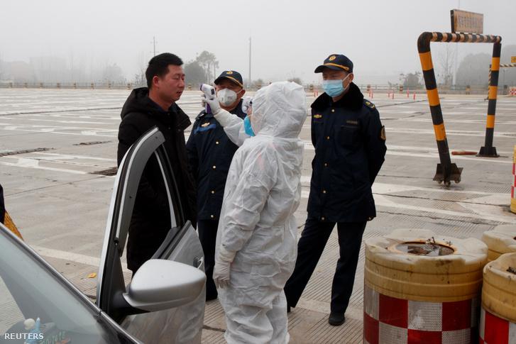 Egészségügyi dolgozó ellenőrzi a testhőmérsékletet Yueyang külterületén Kínában 2020. január 28-án