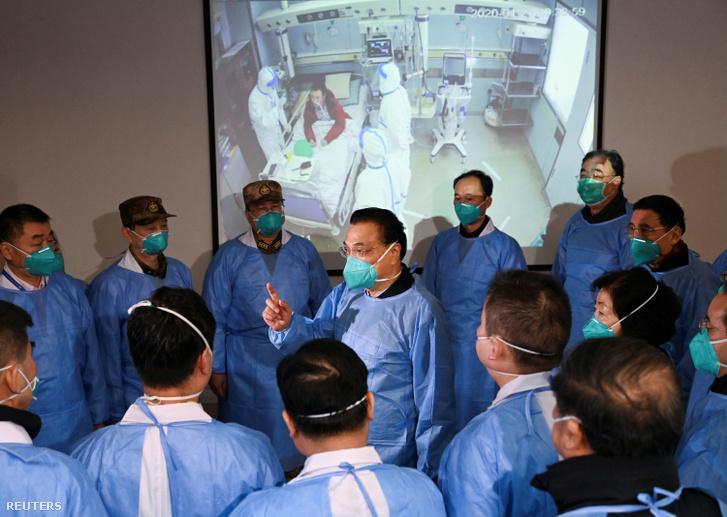 Li Keqiang, a kínai miniszterelnök maszkot és védőruhát viselve beszél az egészségügyi dolgozókkal a Jinyintan kórházban Vuhanban 2020. január 27-én