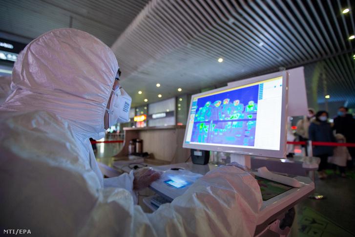 Az utasok testhőmérsékletét ellenőrzi infravörös hőkamerával egy védőfelszerelést viselő egészségügyi dolgozó a kelet-kínai Nancsing nagyváros déli vasúti pályaudvarán 2020. január 27-én.