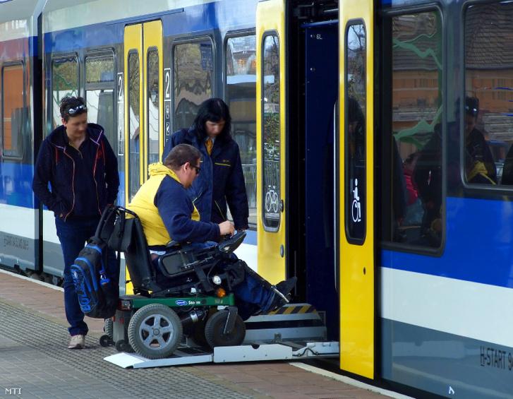 Egy elektromotoros kerekesszékben közlekedő fiatalember a MÁV Start Zrt. munkatársainak segítségével vonatra száll a váci vasútállomás peronjáról.