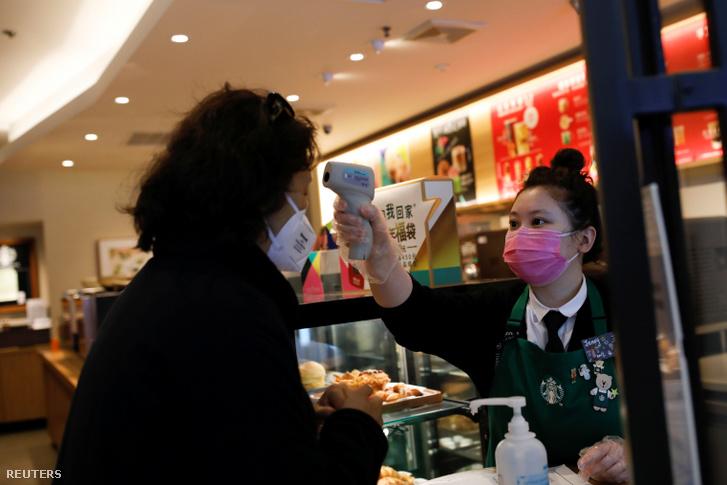 Pekingi kávézóban ellenőrzi a testhőmérsékletét az eladó a betérő vásárlónak 2020. január 30-án
