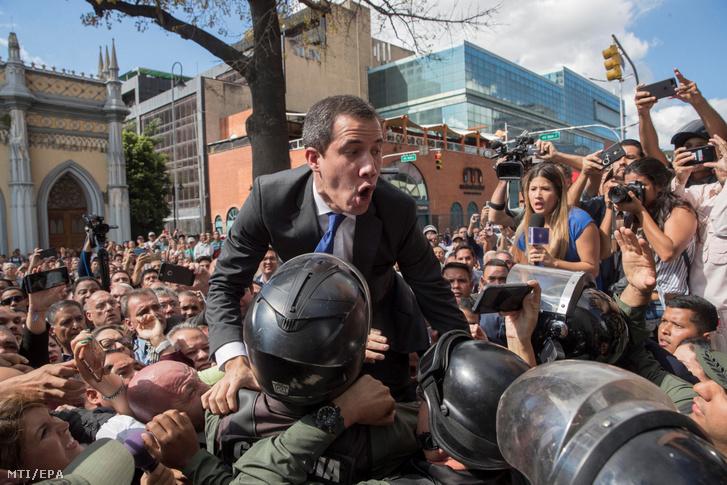 Juan Guaidó, a venezuelai ellenzék vezetője (k) és képviselőtársai áttörik a katonai rendőrség kordonját a parlament bejárata előtt