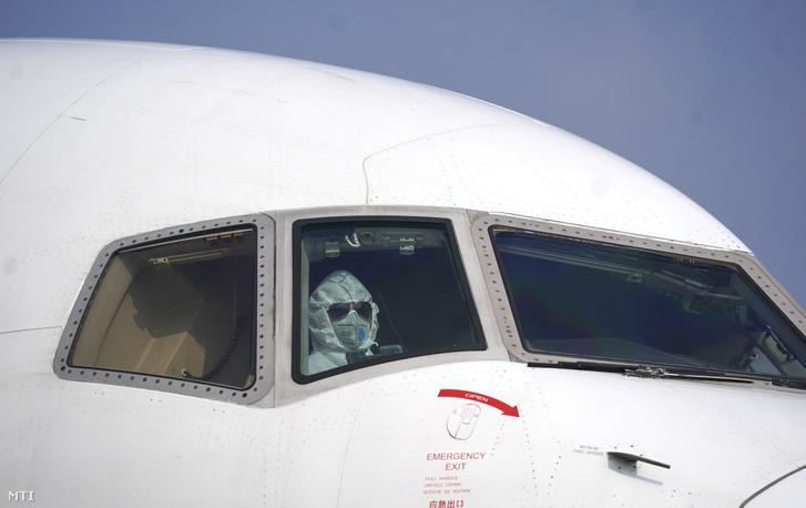 Védőruhát viselő pilóta egy teherszállító repülőgépben a Vuhan-Tianho nemzetközi repülőtéren 2020. január 28-án.