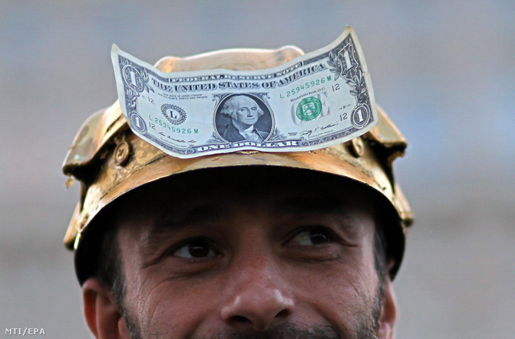 Egydolláros bankjeggyel és aranyozott bányászsapkával a fején vesz részt egy férfi az erdélyi Verespatak mellett tervezett ciántechnológiás aranybánya elleni tüntetésen a parlament bukaresti épülete előtt 2013. szeptember 21-én