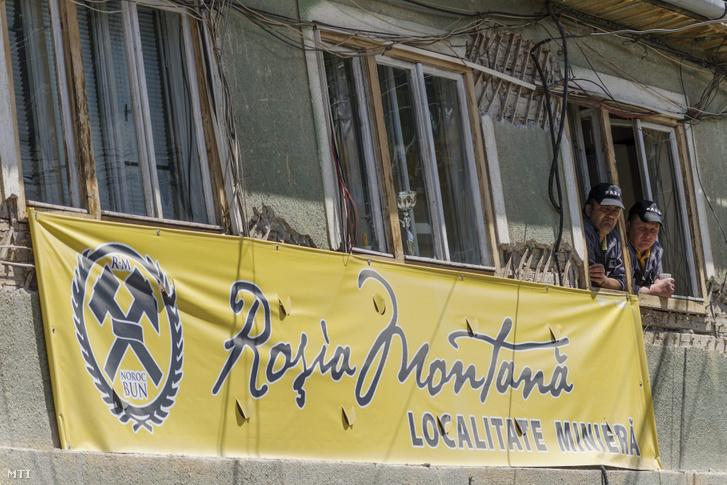 Férfiak egy ház ablakában az erdélyi Verespatakon 2014. május 11-én. A közelbe tervezett ciántechnológiás aranybánya ellen több alkalommal szerveztek demonstrációt az Erdélyi Magyar Néppárt (EMNP) és az Erdélyi Magyar Nemzeti Tanács (EMNT) szimpatizánsai a településen.