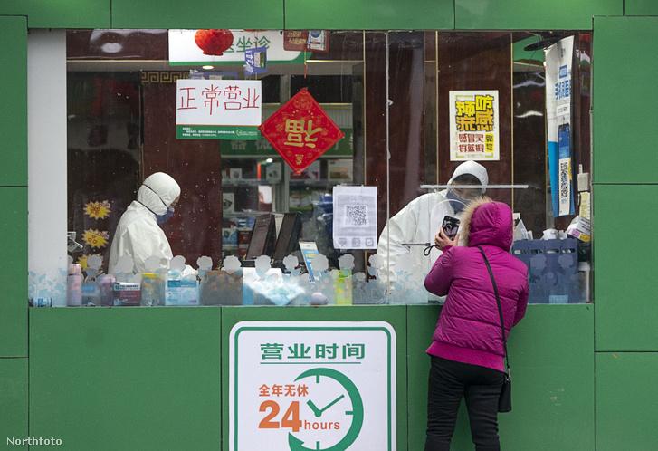 Egy nő vásárol gyógyszert Wuhanban egy patikában 2020. január 26-án