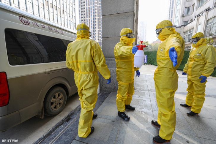 Temetkezési dolgozók fertőtlenítik egymást, miután egy testet leszállítottak a vuhani kórházba 2020. január 30-án