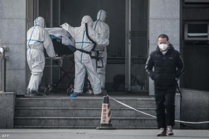 Egészségügyisek szállítanak egy beteget, aki a koronavírussal fertőződött a vuhani Jinyintam kórházban 2020. január 18-án