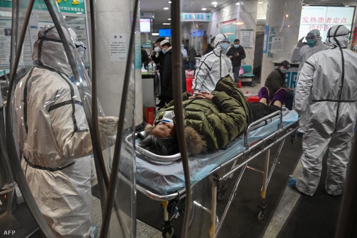 Védőruhában szállítanak egy koronavírussal fertőzött beteget a vuhani Vöröskereszt kórházban 2020. január 25-én