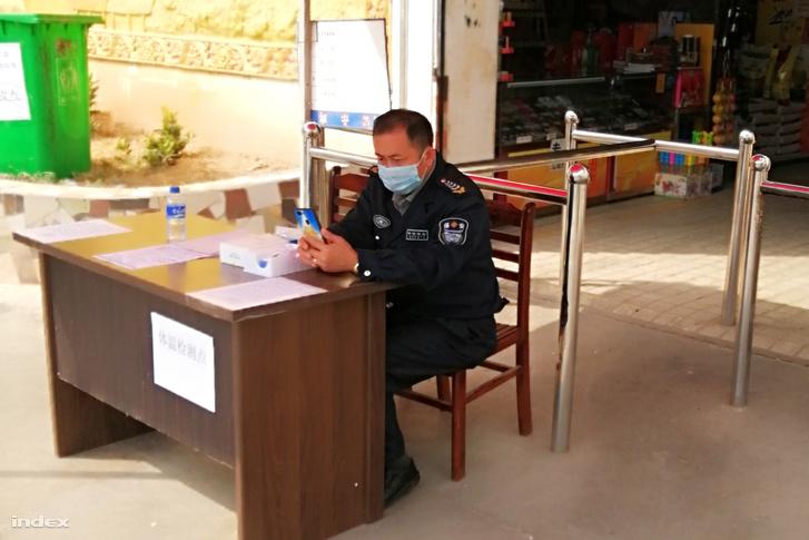 Bevásárlóközpontnál szájmaszkban posztoló biztonsági őr Csinghongban 2020. február 1-én