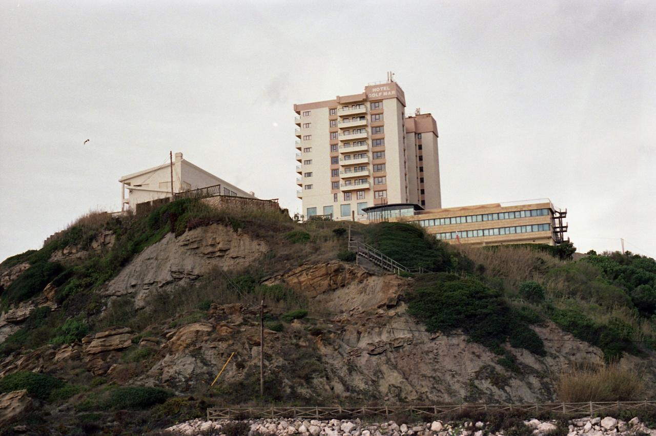 """Hotel Golfmar Vimeiro - a Lisszabontòl északra lévő szálloda az egykori elit kedvelt golfközpontja volt, az 1974-76-os menekültválságban a golfozók együtt voltak itt jelen az afrikai gyarmatokròl visszatelepülő emberekkel.Amikor Portugália 1974-75-ben globális gyarmati hatalomból néhány hónap alatt visszazuhant az európai perifériára, 800 ezren tértek vissza az afrikai kolóniákról az anyaországba. Miközben a fekete többségnek a dekolonizáció függetlenséget jelentett, a nagyrészt fehér portugál """"telepeseknek"""" félelmet, bizonytalanságot és az addigi otthonuk elvesztését."""
