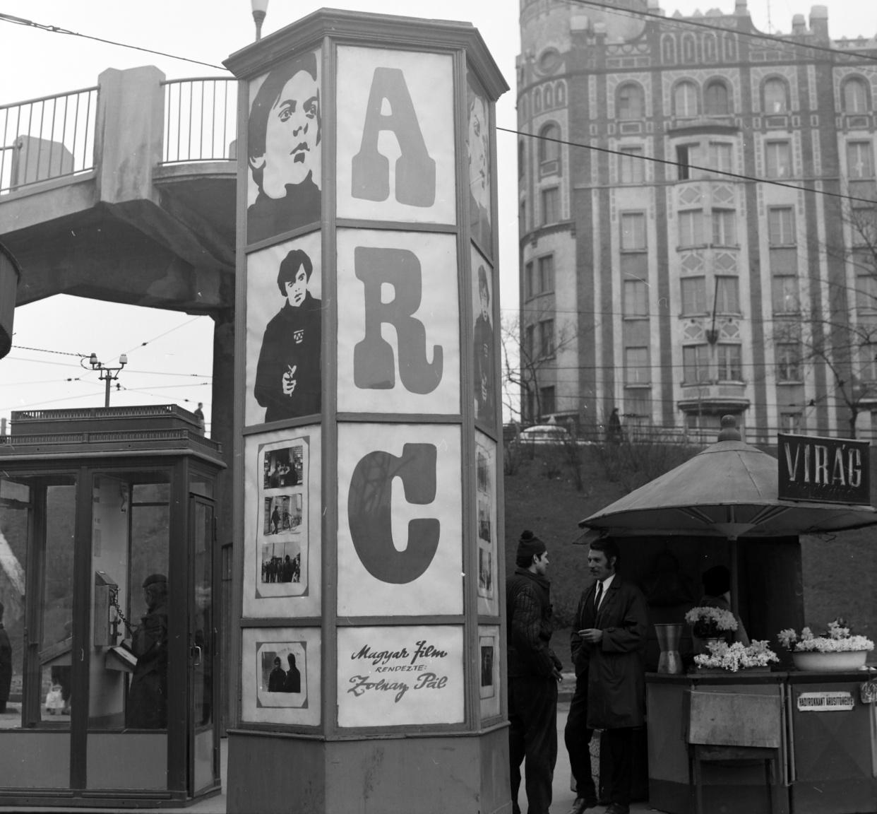 """Az Arc másik, jóval ismertebb és forgalmasabb hirdetési helye a Moszkva téri gyalogos felüljáró alatt egy hatszögletű, speciális üvegezett oszlop volt. A háttérben jól látható a Postapalota, a hirdető oszlop bal oldalán igényes kiállítású kettős telefonfülke, a jobb oldalán virágos bódé. Az eladó sötét sapkában alig látszik, a nárciszra és jácintra korlátozódó virágok árát – 7 Ft egy csokor – krétával írt felirat hirdeti. A mellettük cigarettázva beszélgető furcsa pár egyik tagja feltűnően elegáns, széles barkójú férfi, fiatalabb társa – jóval szerényebb barkóval – kötött sapkában és pufajkában támasztja az oszlopot. A legmeglepőbb talán a bódé oldalán olvasható felirat: """"hadirokkant árusítóhelye."""""""