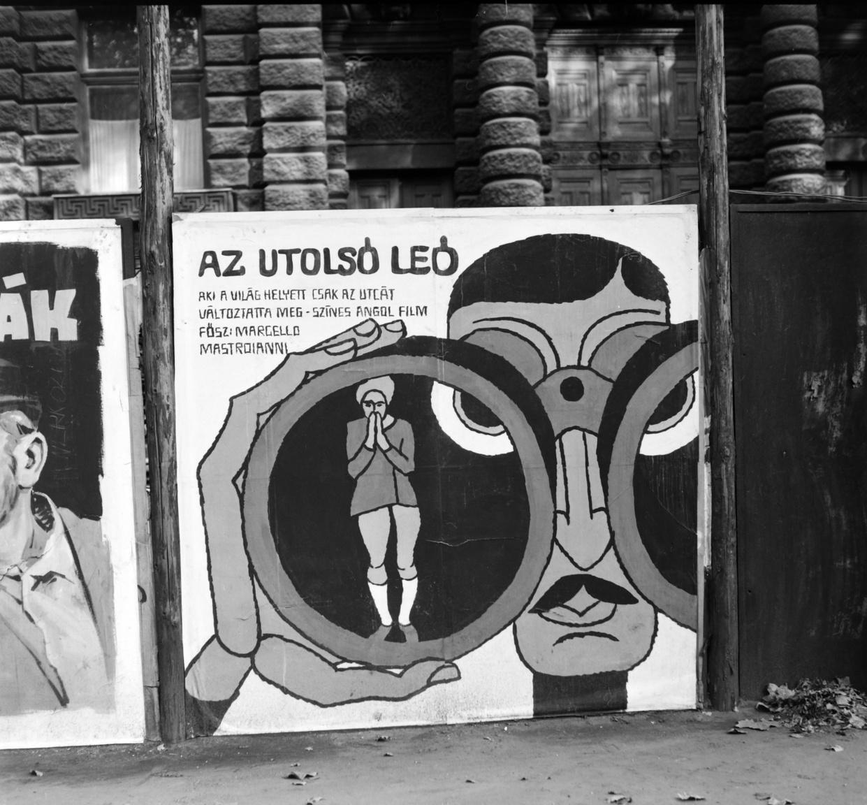 """Az utolsó Leó című filmet (1970, R. John Boorman), angol víg dráma műfaji besorolással az ifjabb nézőknek szánták. A komikus plakát egy elegáns, gondosan elválasztott hajú, komolykodó urat ábrázol, aki távcsőbe bújva figyeli közvetlen környezetét. A felirat is kifigurázza igyekezetét: """"Aki a világ helyett csak az utcát változtatta meg."""" Marcello Mastroianni neve természetesen még ráfért az utcai alkotásra. A plakátok alakja figyelemreméltó, ugyanis a négyzetes elrendezés meglehetősen ritka volt, Az utolsó Leó esetében le is maradt az előregyártott téglalap alakú kép jobb széle. A hirdetési felületet az Andrássy úti (Néphadsereg út) Bábszínház aládúcolt épülete adta (1971)."""