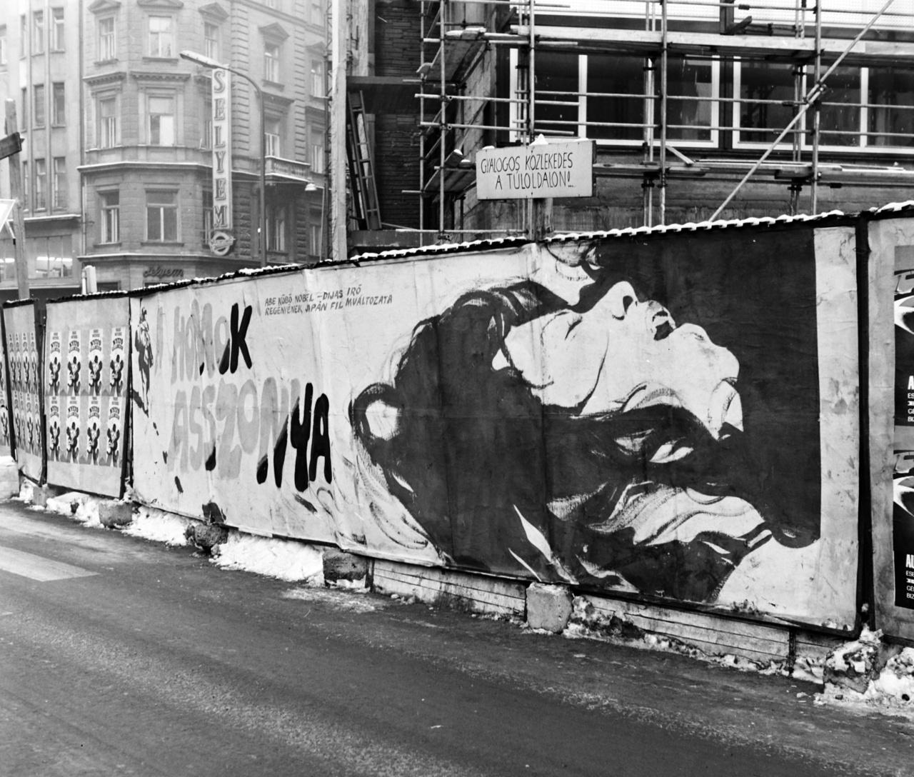 A homok asszonya Cannes-i fesztiváldíjas díjas film (r. Tesigahara Hirosi, 1963) kifejező, a szenvedéstől eltorzult arcú nőt fekvő testhelyzetben és szétbomlott hosszú hajjal megragadó pannóját a Martinelli téren állították ki. A filmet 1971 januárjában mutatták be itthon. A fotó a háttérben látni engedi a Bécsi utcai ház falára erősített Selyem feliratú fényreklámot. A Gyalogos forgalom a túloldalon tábla sokáig maradhatott itt, mert az Országos Műszaki Fejlesztési Bizottság (OMFB) székházát csak 1973-ban adták át.