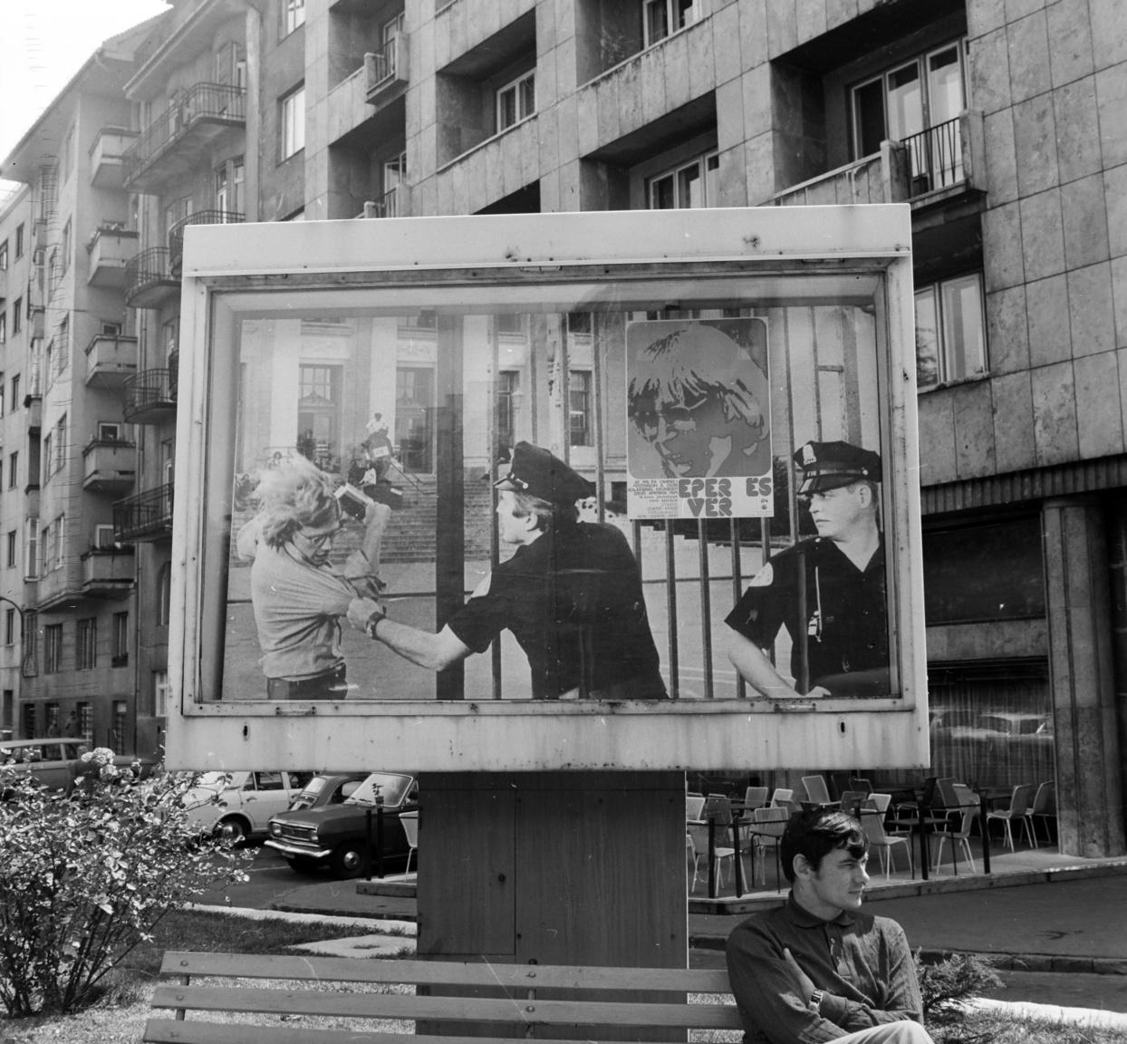 A Mechwart liget sarkán egy villamosszekrényre szerelt hirdetőfelületen az Eper és vér című amerikai film standfotója van kinagyítva, rajta a Mahir és Mokép emblémákkal ellátott kisméretű nyomtatvány. A háborúellenes filmet itthon 1971-ben mutatták be. A háromalakos fotón a főszereplő, kezében könyvekkel dulakodik egy rendőrrel, míg a másik figyeli őket az egyetemi épület előtti börtönrácsra emlékeztető kerítés tövében. A Mokép plakátot úgy ragasztották fel, mintha a nagy fotón látható kerítésen függene. A hirdetésről készített fényképen jól látszanak egy azóta megszűnt presszó utcára helyezett asztalai, a zsúfoltnak nem tűnő parkoló tőszomszédságában