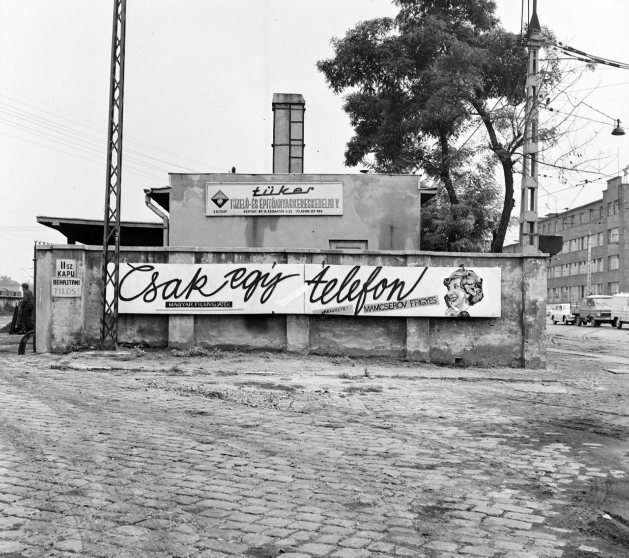 A Fiumei út, 1959 és 1990 között Mező Imre út és a Kőbányai út találkozásánál, a József városi pályaudvar előtt állt a Tüker, a Tüzelő és Építőanyagkereskedelmi Vállalat udvarán a kiszolgáló épület, melynek külső falát a Fömo gyakran használta a filmek reklámozására. A terület az ipari és a lakóövezet határán meglehetősen elhanyagolt, a macskaköves úttest saras, a kép jobb oldalán parkoló kis Zsuk teherautók láthatók, a mögöttük lévő háromemeletes irodaépület tetején kivehető a vörös csillag alakja. Mamcserov Frigyes 1970-ben rendezett filmje, a Csak egy telefon hirdetését nem bonyolították túl, a telefonzsinórra emlékeztető folyóírás mellett Ruttkai Éva mosolygós képmása erősíti meg a mondandót – ez egy vígjáték.