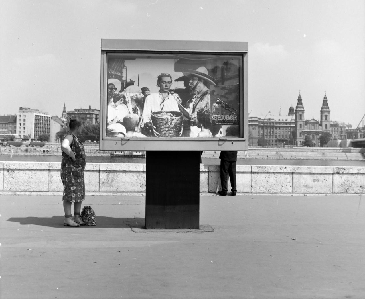 """Az 1962-es szovjet sci-fi, a Kétéltű ember (Gennagyij Kazanszkij - Vlagyimir Csebotarjev) felújított változatát (1971) egy kinagyított standfotóval hirdették a Batthyány téren. Az üvegezett hirdetőtábla jobb oldalára pedig egyszerűen betettek egy kis alakú """"villamos plakátot"""", aminek grafikája nem igazán illeszkedett a fotóhoz. A földre helyezett táskával várakozó nő, a fotós kérésére vagy talán árnyékot keresve állt félre és fordította arcát a Duna és az Erzsébet hír irányába."""
