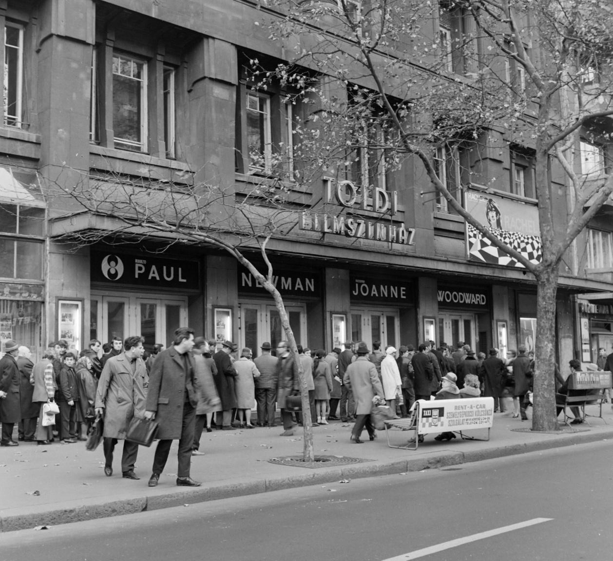 A Toldi filmszínház előtt sorok állnak, feltehetően a plakáton hirdetett, kétszeres Golden Globe díjazott Rachel, Rachel című amerikai film miatt (R. Paul Newman, 1968). A padok háttámláin angol-magyar nyelvű hirdetés: Taxi. RENT A CAR. Személygépkocsi-kölcsönző szolgálat és Ruhatisztító Szövetkezet. A két fiatal férfi éppen a forgalmat figyeli mielőtt átvágna (szabálytalanul) a Bajcsy-Zsilinszky úton. A filmet itthon 1970-ben tűzték műsorra a mozik.