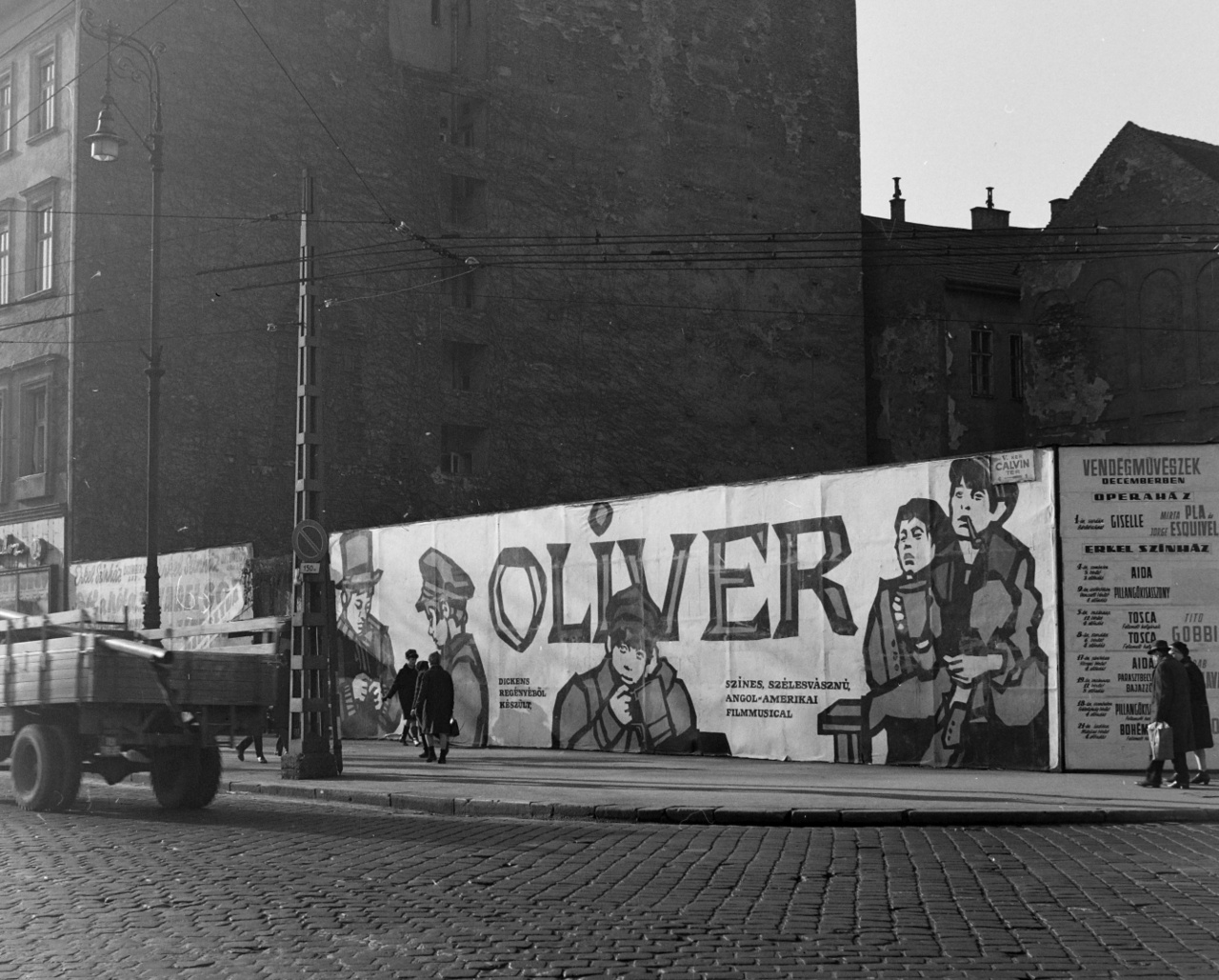 A Twist Olivér történetét feldolgozó Oliver című film Dickens regényének adaptációja volt. A musical 153 perces filmváltozata (Oliver! r.: Carol Reed) 1968-ban készült el, és ma is a legjobb 100 brit film között tartják számon. Itthon 1971-től láthatták a nézők.                          A fotón a járdán sétáló emberalakok mérete jól mutatja milyen óriási méretű plakátok fedték a Kálvin tér 1 sz. foghíjtelkét körülvevő palánkot. A grafika mintha mesekönyvillusztrációt idézne: öt szomorú, 19. századi öltözetű fiú néz a járókelőkre. A cím betűi is könyvszerűek, kis játékosságot engedve. A ködös angliai hangulatot fokozza az enyhén sötét, homályos fotó, ahol a macskaköveken egy túlméretezett csövet szállító régi, fadeszkázatú teherautó hajt keresztül. A filmplakát két oldalán az Operaház és az Erkel színház hirdeti műsorait olyan sztárokkal mint a kubai Mirta Pla és Jorge Esquivel balettáncosok, vagy az olasz bariton, Tito Gobbi. A kép baloldalán, az első épület aljában fényképész üzlet hirdeti szolgáltatásait, míg a jobb alsó sarokban egy autó suhan ki a képből.