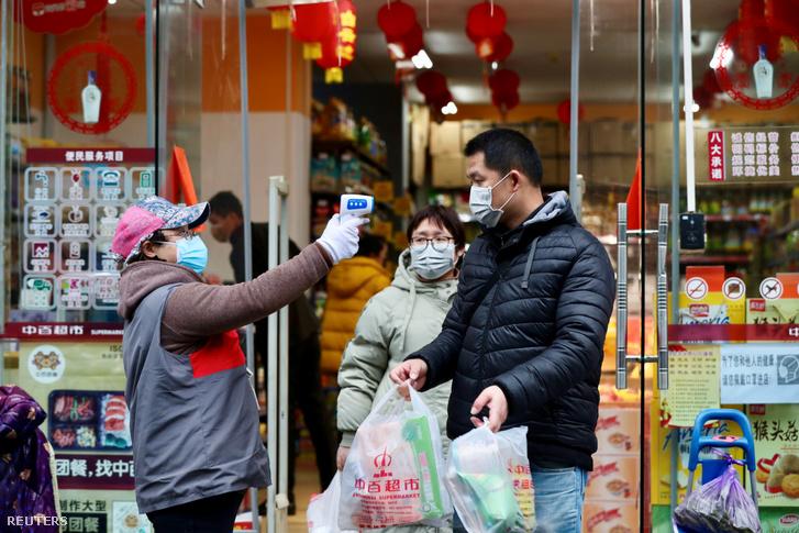 Dolgozó ellenőrzi a vásárlók testhőmérsékletét egy vuhani szupermarketnél 2020. február 7-én