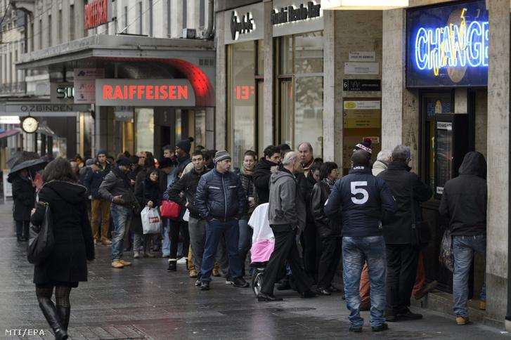 Sorban állnak az ügyfelek egy genfi pénzváltó előtt 2015. január 16-án. Az előző nap a svájci jegybank a Svájci Nemzeti Bank eltörölte a svájci franknak az euróval szembeni árfolyamküszöbét és az ez után megerősödő frank miatt a svájciaknak előnyös a frankjukat euróra váltani.