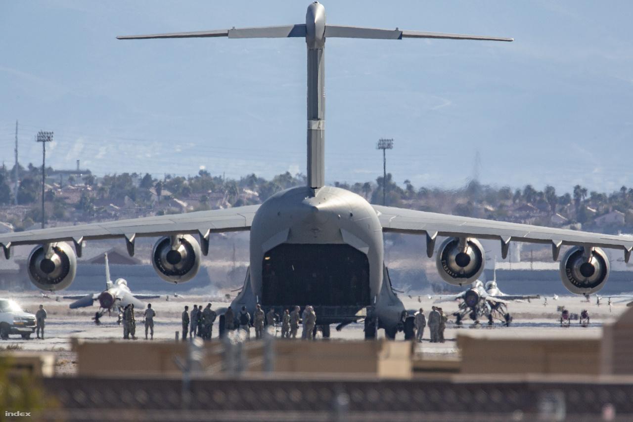 Tovább haladva újabb tökéletes látványban volt szerencsém: az elébb látott repülőgépfaroknak meglett a tulajdonosa, egy pompás Boeing C-17 Globemaster III. A gép rámpáját pont ekkor kezdték felhúzni, a fényképezőgép optikáján keresztül még azt is láttam, hogy bent katonák álldogáltak vagy készültek leülni, miközben a betonon tucatnyian beszélgettek. A levegő a repülőgép hajtóműveiből kiáramló forró gázoktól remegett, kissé elmosva a távolabb megpillantott F-16-os vadászgépek sziluettjeit.